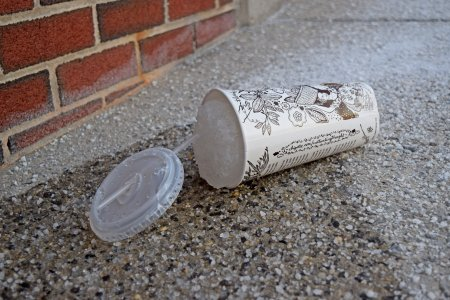 A discarded Chipotle cup filled with a frozen beverage.