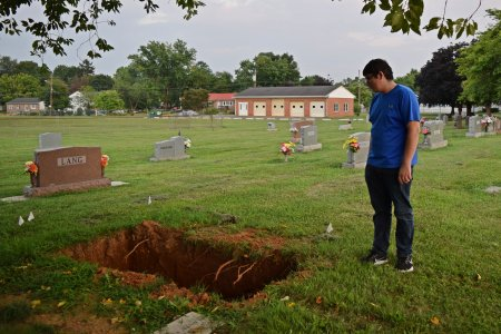 Aaron stands next to an open grave, contemplating life.