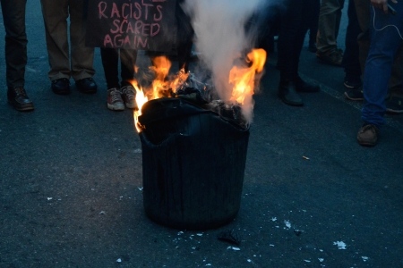 The trash can, buckling as its contents burn.