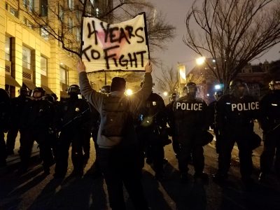 "Holding a ""4 Years To Fight"" sign in front of a row of police in riot gear."
