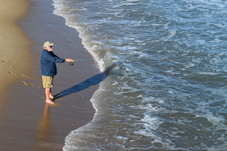 A man goes fishing in the ocean.  Was surprised that he was walking around barefoot!