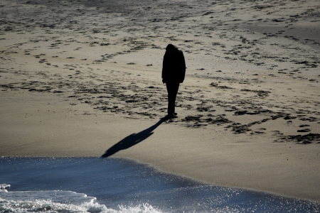 A person walks along the beach, south of the fishing pier.