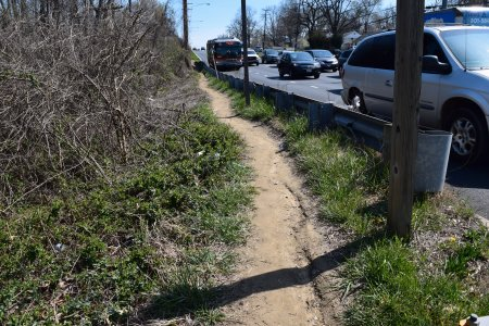 Well-worn desire path along the side of westbound Veirs Mill Road.  There are no sidewalks in this area, and this path runs from Havard Street all the way to the subject crossing at the bottom of the hill.