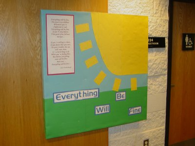 "I still don't understand why I made this bulletin board.  It shows grass, sky, and a big, yellow sun, with the words ""Everything WIll Be Fine"", along with the lyrics to a song that starts the same way from Today's Special.  I remember not being pleased with how that sun came out.  I put it up during a massive snowstorm, and so I'm pretty sure that this board, as well as the next one, were made using materials that I already had on hand due to the aforementioned snowstorm."