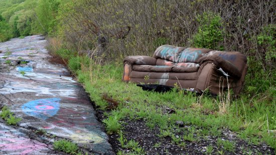 A couch, abandoned on the side of the road, and also covered with graffiti.  Surprisingly, this was not the only abandoned couch that I found here.