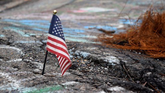 An American flag, stuck into one of the cracks in the old road.