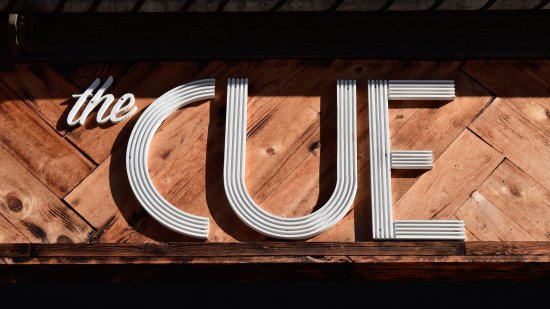 Sign for The Cue, which is a Christianity-focused meeting space.  I don't think that the sign is necessarily vintage, but the wood backdrop and fonts definitely threw back to an older period.