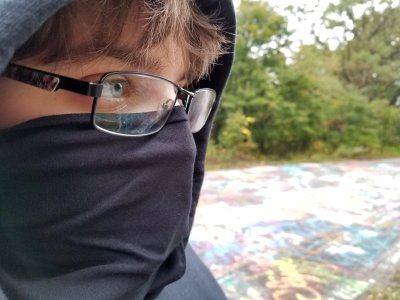 "Elyse wears a black bandanna as a filter for spray paint fumes while she was tagging.  I put her in all black for the planned photo set, but the bandanna was her own idea.  I laughed, because Elyse was dressed in ""full black bloc"" for the purpose of tagging the abandoned road."