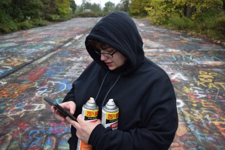 Elyse holds her spray paint cans while checking her phone.