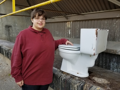 Elyse poses for one final photo with the old commode at the Shady Grove Transfer Station.