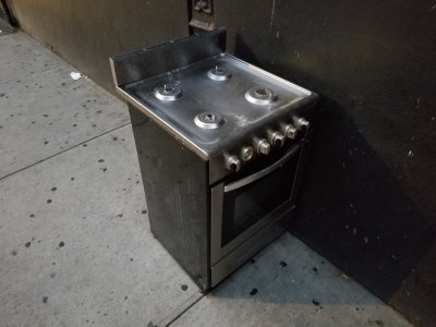 A gas stove sitting on the sidewalk
