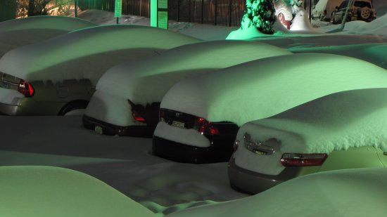 Cars parked along the side spaces, with a significant amount of snow accumulation, though nowhere near as much as the cars alongside the building got.