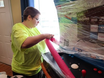 Elyse gets to work unwrapping the arcade machine.
