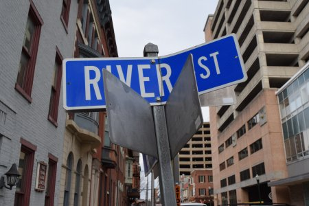 Bent street signs at the intersection of River and Walnut Streets.
