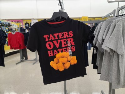 "Kid-sized shirt in the clothing section, reading ""taters over haters""."