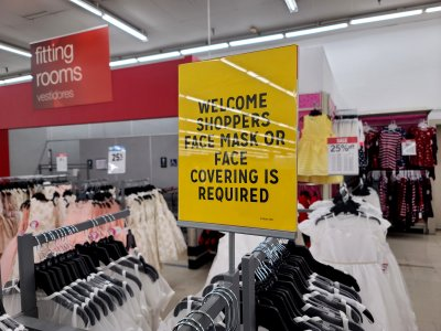 Face mask signage in the clothing section.  The fitting rooms, visible in the background, were closed because of coronavirus.