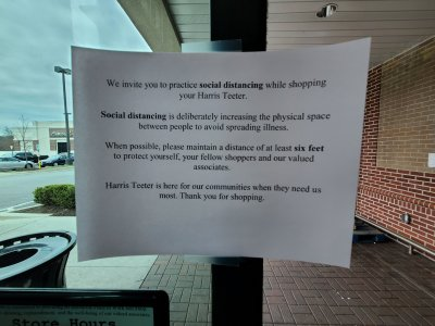 Sign on the door at the Harris Teeter in Ellicott City asking people to practice social distancing.