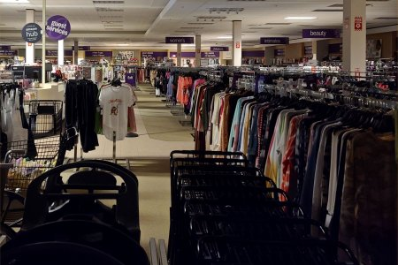 Long racks of clothes on the right side of the store. Long racks of clothes like that are a typical arrangement for an off-price store.