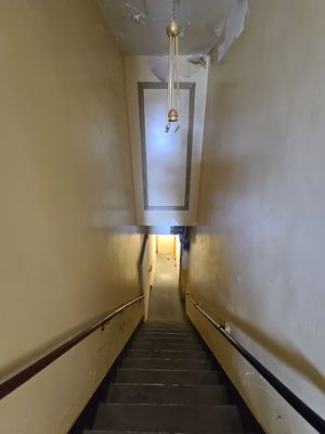 Stairway leading up to the penthouse from the rest of the hotel. This stair is the only way to access the penthouse level. The stairs were in rough shape, with a large chip out of at least one step.
