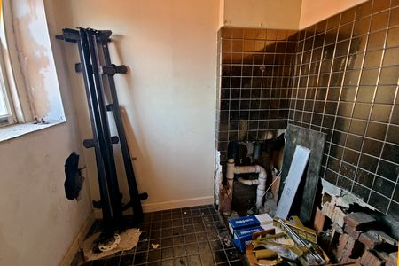 Full bath. The black tile that you see here is not original, based on the presence of even older tile beneath it on the floor around the toilet flange. However, all of the various bathroom fixtures, including a toilet and bathtub, have been removed.