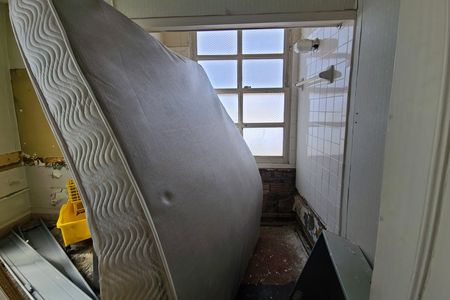 Big mattress being stored in one of the rooms. A second full bath is visible behind this.