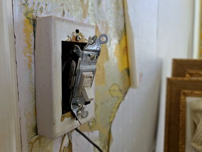 Another light switch. Note the old wallpaper that is peeling, which covered even older wallpaper behind it.