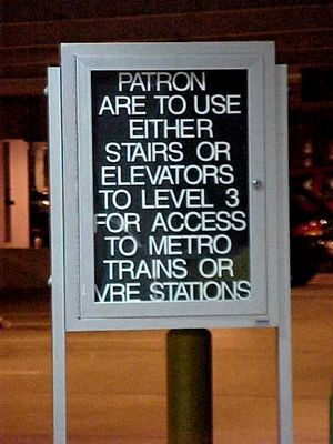 Signs in the parking garage at Franconia-Springfield. One sign explains how to get to the station from the garage, and the other has been modified by a prankster to endorse the passing of gas while on television.