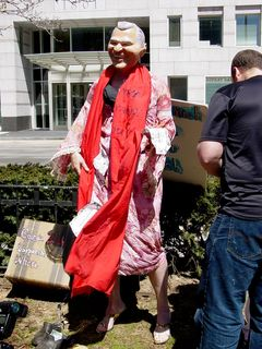 """And, as mentioned earlier, this is Georgia Bush, the """"Georgia Corporate Whore"""", according to her suitcase, complete with dress, red sash, and rubber Bush mask."""