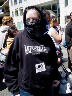 """A masked woman wears an anti-fascist sweatshirt, while also wearing a """"60 Years of Destruction"""" sticker. Sis and I also wore these stickers, which were being given out at the rally site."""