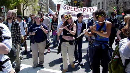 A group plays flutes while marching, providing a different style of music. They can he heard in the above movie clip.