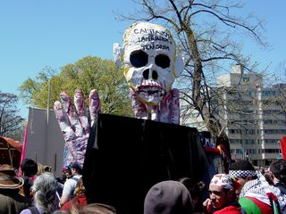 The George W. Bush/skull street puppet rises high above the crowd.