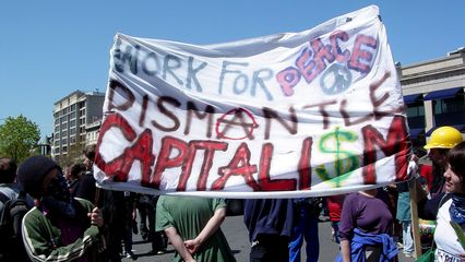 """The sign seen from behind in the previous movie reads, """"Work for peace, dismantle capitalism""""."""