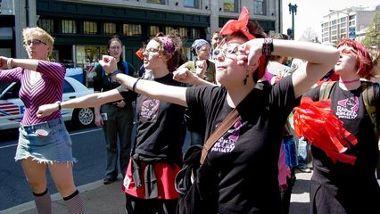 A group of radical cheerleaders does a cheer in the street at Dupont Circle.