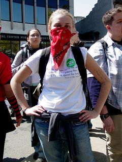 """A masked woman wears a shirt saying """"Fight for the right, not for the wrong/Going there, I'm growing there/Helping the weak against the strong."""""""
