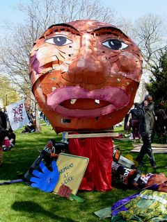 The largest of the street puppets by far, wheeled near the front of the march, made it in one piece. Other props used in the march lay on the ground around it.
