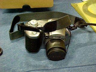 Soon after, I hooked on the essential equipment.  The lens cap is tied on, just like on the old Mavica, plus the neck/shoulder strap is now attached.  A new feature was that the middle of it had a piece of rubber attached to it.