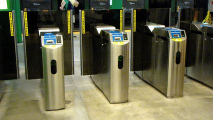 Faregates at Copley. When exiting a T station, since the MBTA charges a flat fare for rail travel, you simply walk through the gates, and the gate pops open when it detects someone heading towards it.