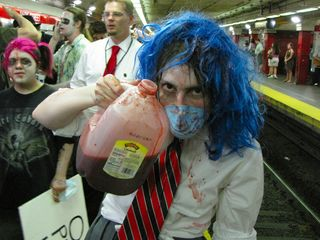 Blue Wig Girl, having made herself sufficiently bloody, holds up a milk jug containing more fake blood.
