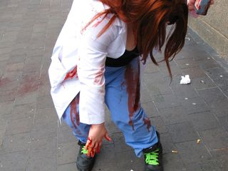 A soon-to-be zombie applies blood on her clothing.