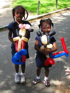 Two very adorable children with really awesome face paint, holding what are most likely the most complex balloon animals that I've ever seen.