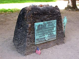 The headstone for Samuel Adams, and the stones and coins placed atop it.