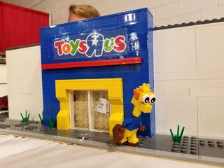 """Toys """"R"""" Us by Jackson McCoy, showing Geoffrey the Giraffe leaving the store for the last time, with a sign reading """"No more toys"""" on the door."""