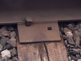 """As we were approaching Chicago, we stopped for a moment, and I got a moment to look at a railroad tie plate. I find it interesting how each plate is stamped with identifying information, though I have no idea what any of it means, unfortunately (though I presume that the """"Weirton"""" part refers to Weirton Steel)."""