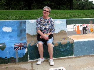 Mom poses for a photo while sitting on another section of the same concrete bench.