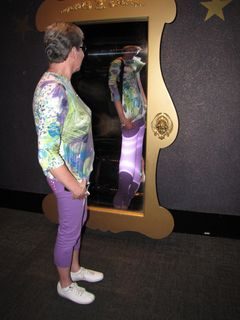 Mom takes a moment to pose in front of a funny mirror.