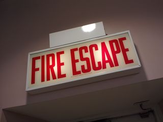 """One thing about Chicago is that the exit signs are different. Local ordinance requires that exit signs be built to very specific requirements, which makes them unique within the city. You also get """"stairs"""" signs, and in this case, in a store on the Magnificent Mile, there is a """"fire escape"""" sign."""