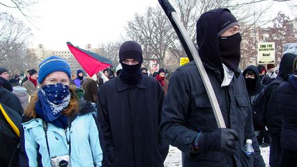 A black bloc, as mentioned earlier, had gathered around the back of the group, but closer to the stage than the police cars. This black bloc was definitely more hardcore than I was accustomed to, as a number of them had items for defending against pepper spray and tear gas close by.