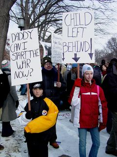 """I particularly enjoyed the sign on the right in this photo. As my mother is a teacher, our family is strongly against """"No Child Left Behind"""" as we find that the program contains some provisions that are beyond educators' control, leaving everyone behind as a result."""