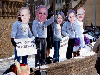 At a street corner, I encountered people wearing large cutout masks representing George W. Bush, Donald Rumsfeld, Condoleezza Rice, and other members of the Bush administration. Another person was also dressed as the hooded Abu Ghraib prisoner that was shown in a photograph first made public in May 2004.