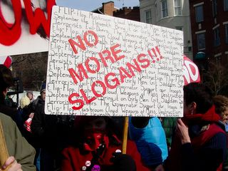 """In the march, I soon met a woman wearing all red and a red bandanna holding up a sign saying """"NO MORE SLOGANS!!!"""" with various slogans we've all heard penned in behind it. The slogans that the poster decries over and over again are """"Flip Flop"""", """"Bring It On"""", """"Girly Men"""", """"The Governator"""", """"Mushroom Cloud"""", """"Weapons Of Mass Destruction"""", """"Git Saddam"""", """"September The Eleventh"""", """"Support Our Troops"""", """"Evil Doers"""", and """"Terrorists""""."""